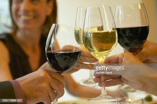 Group of people toasting wine, close-up (focus on glasses and hands)
