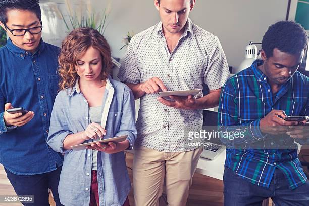 Grupo de personas con dispositivos móviles.