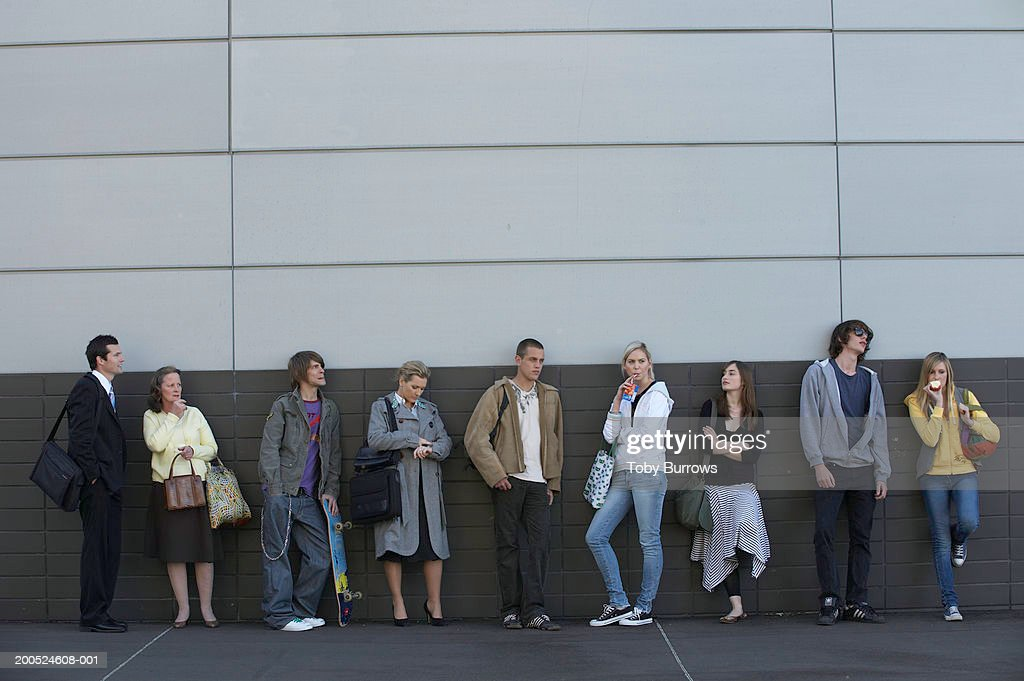 Group of people waiting against wall