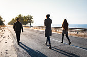 Three young persons walking in beautiful nature scene in late summer or autumn