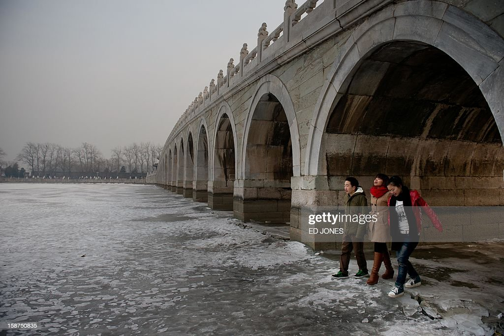 A group of people walk beneath a bridge on a frozen lake at the Summer Palace in Beijing on December 27, 2012. Forecasts were predicting temperatures of around minus 20 degrees in the run-up to January 1. AFP PHOTO / Ed Jones