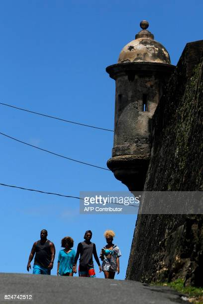A group of people walk by a 17th Century Spanish Fortress stone walls between El Morro and the fort San Cristobal in the neighbourhood of La Perla...