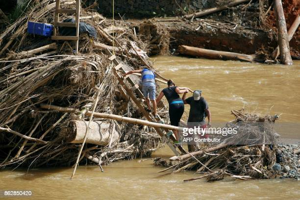A group of people walk over debris on the Vivi River to get access to the Rio Abajo community in Utuado on October 17 2017 The improvised pulley...
