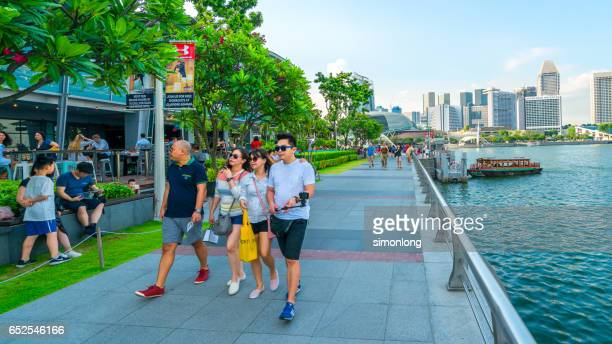 A group of people walking along the sidewalk in Marina Bay, Singapore.