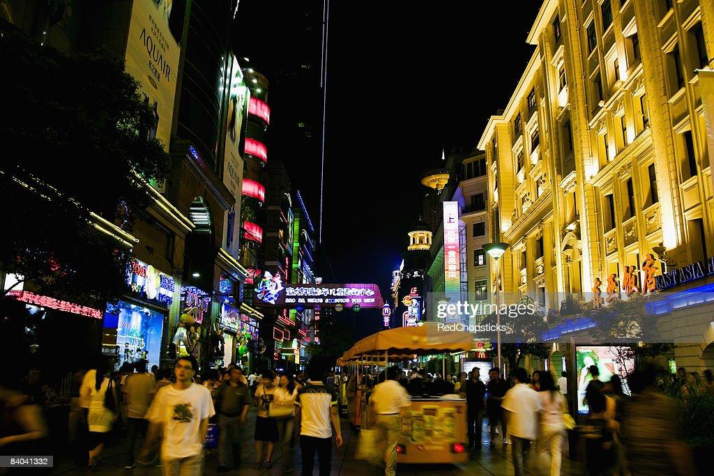Group of people walking in a street at night, Nanjing Road, Shanghai, China