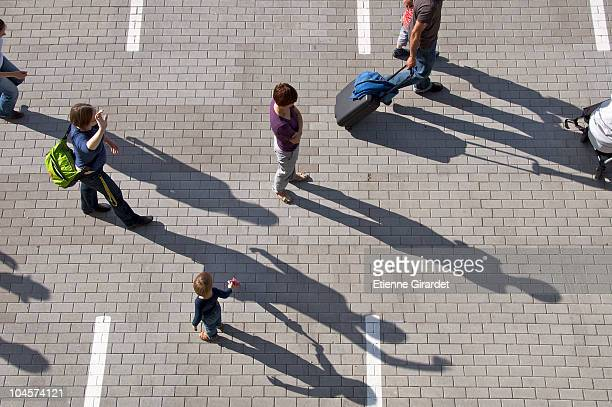 A group of people walking through a parking lot