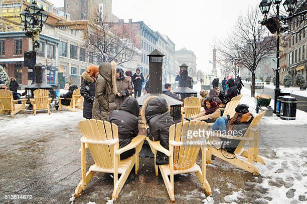 Group of people warming up around public fireplace Old Montreal
