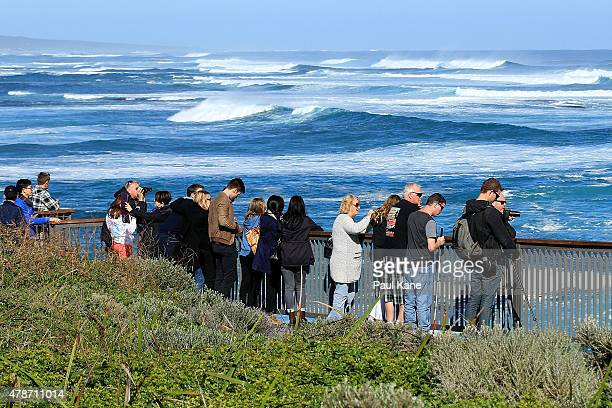A group of people watch large waves at Surfers Point on June 27 2015 in Margaret River Australia Monster swells were predicted for the south west...