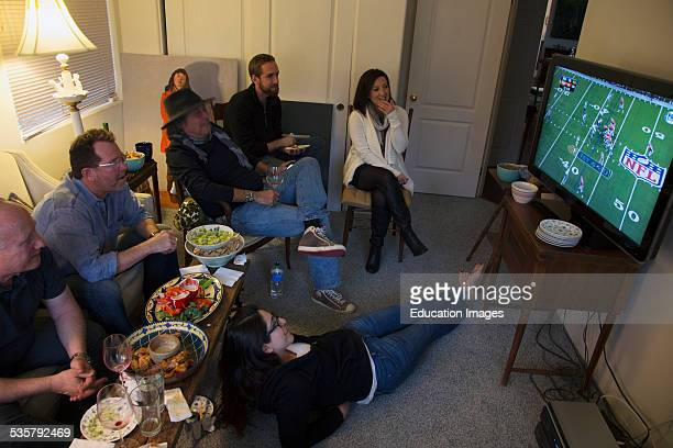 Group of people watch NFL Super bowl XLVIII on television Feb 2 Denver Broncos vs Seattle Seahawks