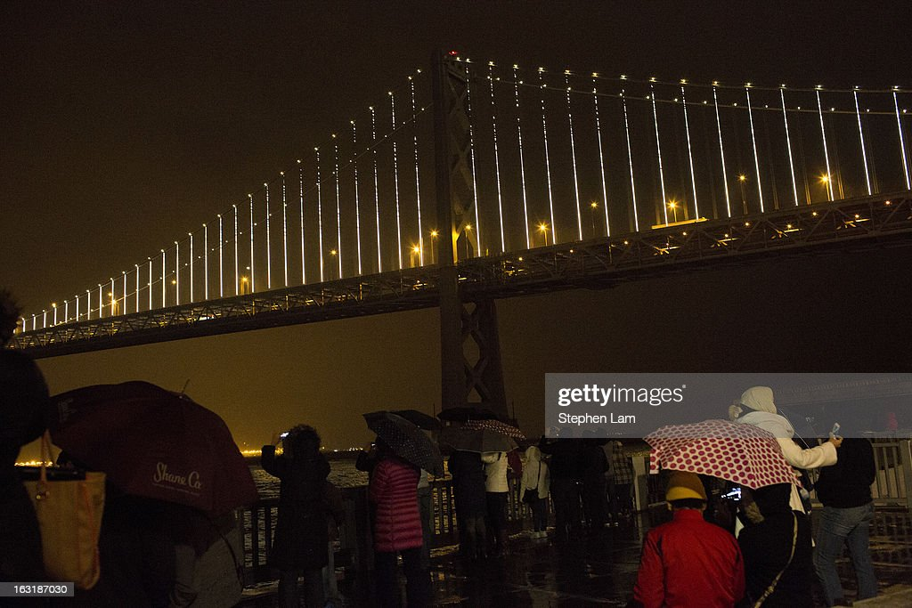 A group of people watch the grand lighting of the Bay Lights art installation on the San Francisco-Oakland Bay Bridge on March 5, 2013 in San Francisco, California. Designed by artist Leo Villareal, the Bay Lights is the world's largest LED light sculpture, spanning 1.8 miles long and 500 feet high with 25,000 individual LED lights. The installation will be on display daily from dusk to 2 a.m. for the next two years