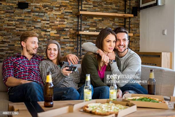 Gruppe von Personen mit Bier vor dem Fernseher und pizza