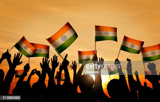 group of people waving indian flags in back lit stock