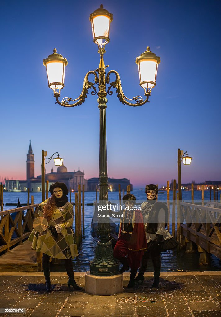 A group of people wearing carnival costumes pose in Piazza San Marco on February 06, 2016 in Venice, Italy. The 2016 Carnival of Venice will run from January 23 to February 9 and includes a program of gala dinners, parades, dances, masked balls and music events.