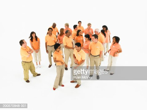Group of people wearing orange polo shirts, elevated view : Stock Photo