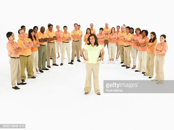 Group of people wearing orange polo shirts forming semi-circle