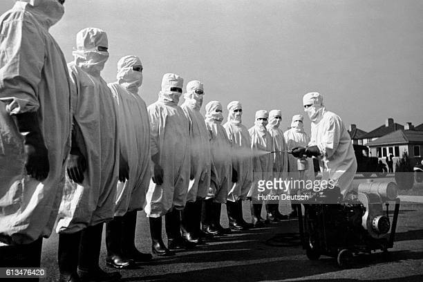 A group of people wearing protective suits are sprayed with a substance possibly a disinfectant to prevent the spread of typhus