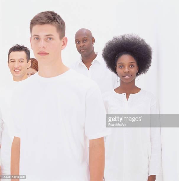 Group of people wearing white, posing in studio, portrait