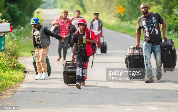 TOPSHOT A group of people who claimed to be from Haiti walk down Roxham road in Champlain New York as they prepare to cross the border into Canada...