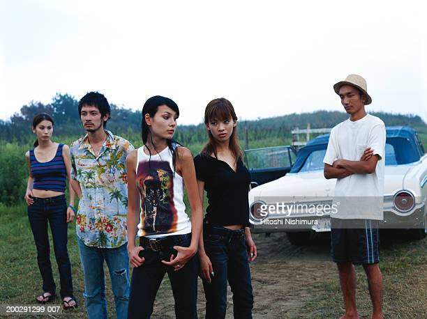 Group of people with car in field, looking away