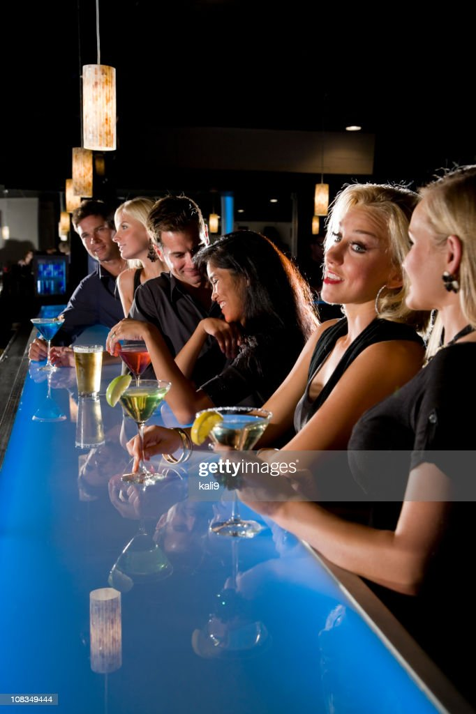 Group of people with drinks at nightclub bar : Stock Photo