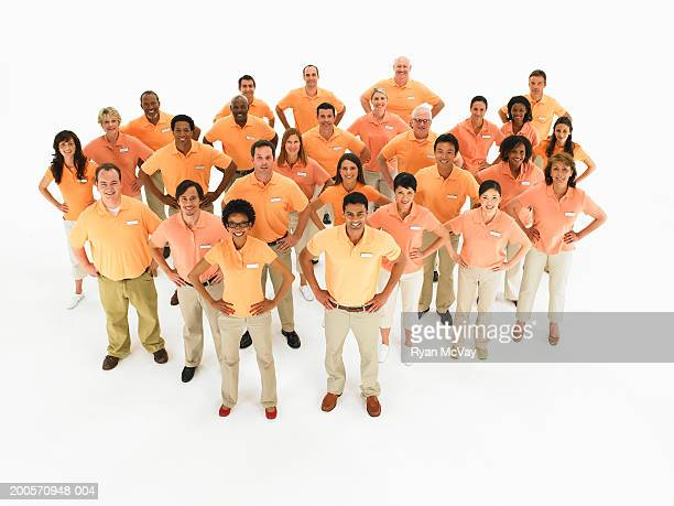 Group of people with hands on hips, wearing orange polo shirts
