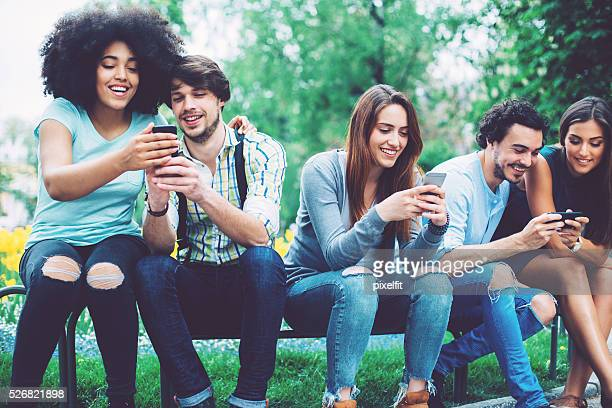Group of people with smart phones in the park