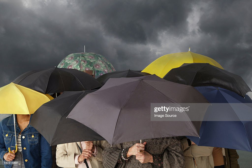 Group of people with umbrellas : Stock Photo