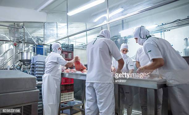 Group of people working at a food factory