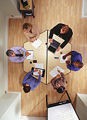 Group of people working at table in office, overhead view