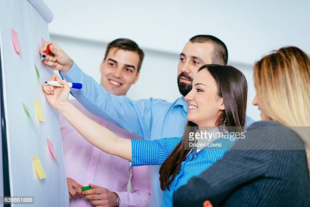 Group of people writing on flip-chart in office