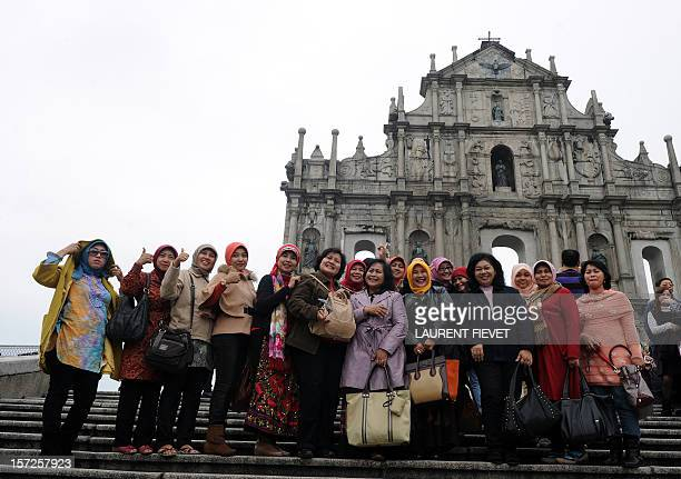 A group of Philipino tourists pose for pictures in front of the Ruins of St Paul the facade of what was originally the Cathedral of St Paul in Macau...