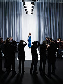 Group of photographers in front of female model walking down catwalk