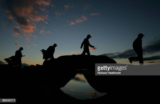 A group of players and caddies walk across the Swilcan Bridge during the first round of the 134th Open Championship at Old Course St Andrews Golf...
