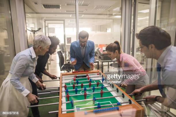 Group of playful business colleagues playing foosball in the office.