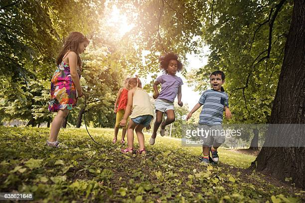 Group of playful kids having fun while skipping jump rope.