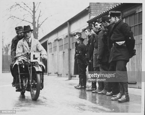 A group of Post Office messengers watch as a driving instructor takes a colleague for an instructional ride on the back of his motorcycle This is...