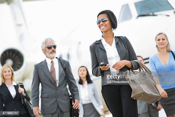 Group of powerful business executives deboarding private company jet