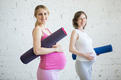 Pregnancy Yoga, Fitness concept. Portrait of two attractive young pregnant yoga models posing with sport mats against white wall indoor. Pregnant smiling fitness women before practicing yoga at class