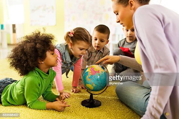 Group of preschoolers examining world globe with their teacher.