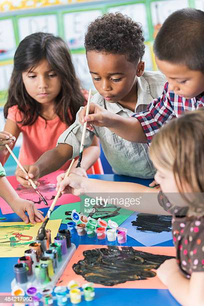 Group of preschoolers in art class painting pictures