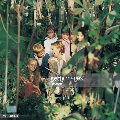 Group of Primary School Children Surounding their Female Teacher on a Field Trip in a Lush Botanical Garden