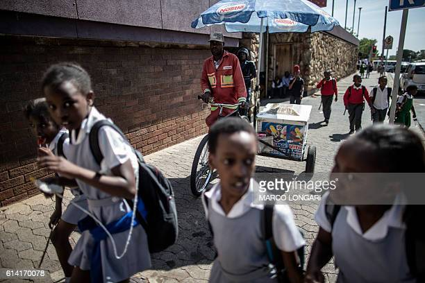 A group of Primary school students walk past an ice cream vendor during a protest a the Hillbrow Magistrate Court by University students on October...
