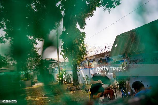 A group of prisoners chat whilst they eat lunch inside the prison yard convicts from some Thai prisons are allowed to train for boxing matches in...