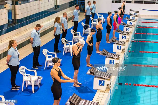 Group of professional female swimmers preparing by the pool