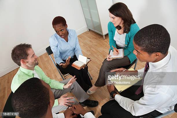 Group of professionals having Bible study in an office environment