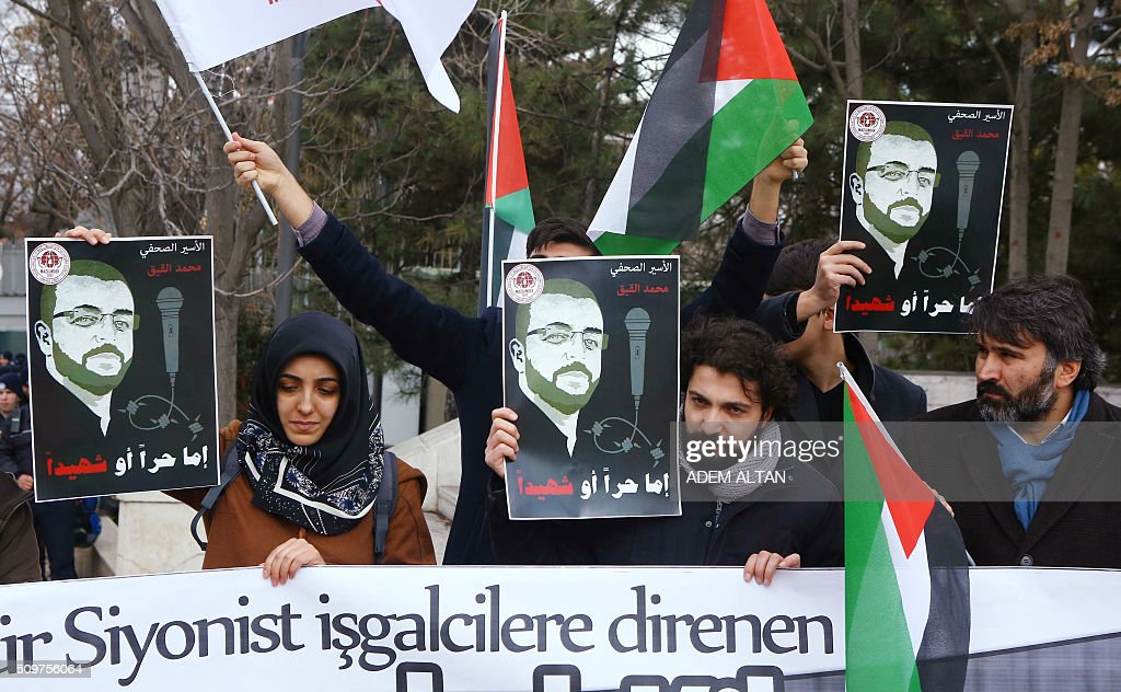 A group of pro-Palestinian hold Palestinian flags and posters of Palestinian journalist Muhammed al-Kik, jailed in Israel, as they stage in solidarity with al-Kik and protest against Israel outside the Israeli ambassador's residence in Ankara, on February 12, 2016. / AFP / ADEM ALTAN