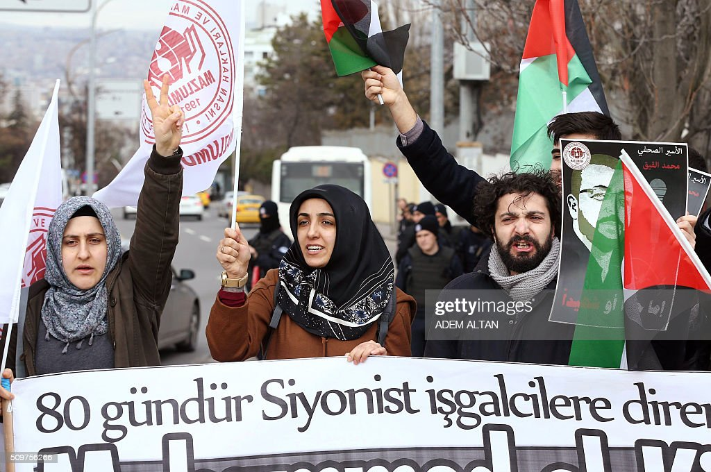 A group of pro-Palestinian hold Palestinian flags and posters of Palestinian journalist Muhammed al-Kik, jailed in Israel, as they stage in solidarity with al-Kik and protest against Israel outside the Israeli ambassador's residence in Ankara on February 12, 2016. / AFP / ADEM ALTAN
