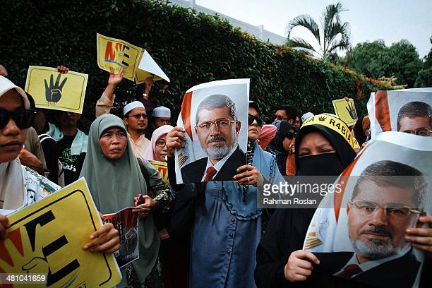 A group of protester hold a poster of Mohammed Morsi Egypt's ousted president during a protest against the mass execution sentence of 529 supporters...