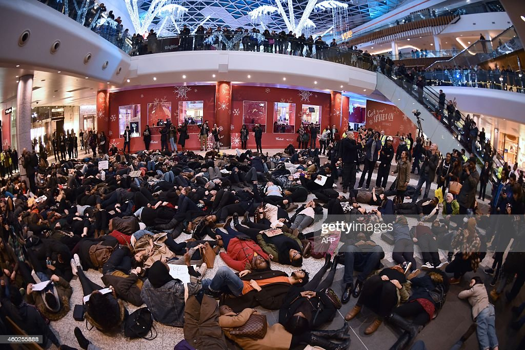 A group of protesters create a 'diein' at the Westfield shopping mall in West London on December 10 in support of protests in the US over the...