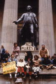A group of protesters demonstrate against nuclear weapons sitting and holding signs beneath the statue of George Washington at Federal Hall Wall...